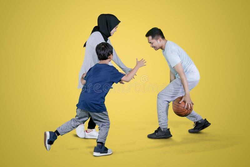 Família muçulmana que joga o basquetebol no estúdio foto de stock