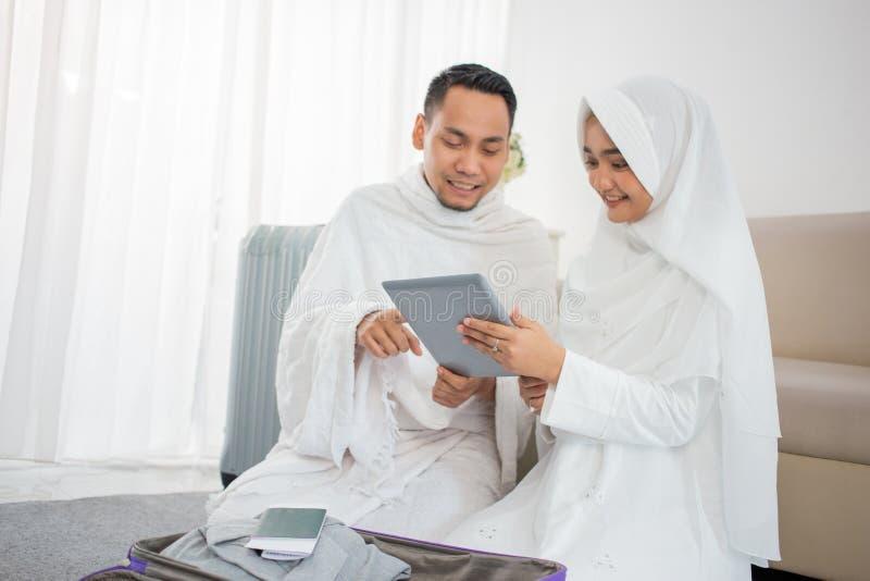 Família muçulmana que prepara a bagagem antes do Haj usando a tabuleta fotografia de stock royalty free