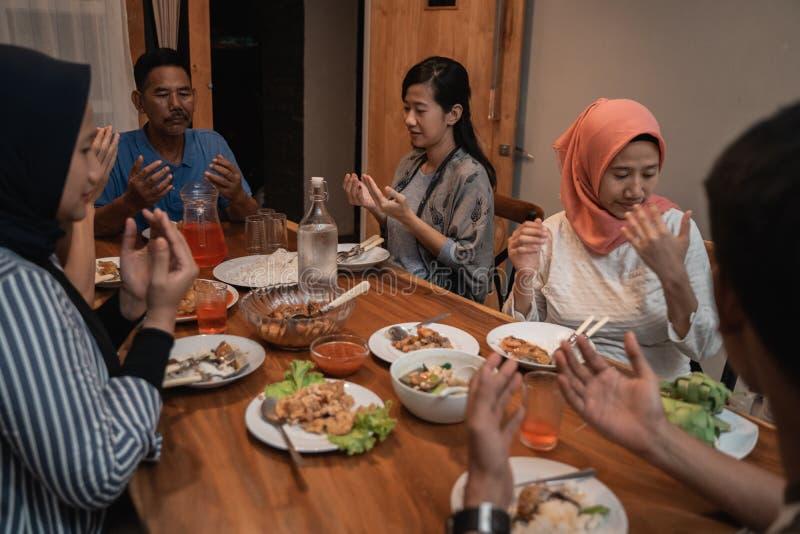 A família muçulmana reza antes do jantar fotografia de stock