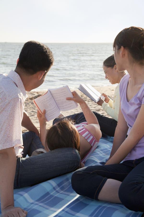 Família Multigenerational que relaxa e que lê na praia imagens de stock
