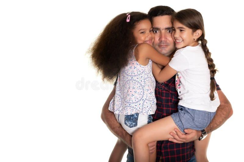 Família multirracial, pai latino-americano com uma expressão engraçada que abraça suas filhas da raça misturada imagens de stock royalty free