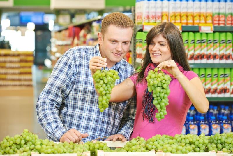 Família na compra de alimento do fruto no supermercado fotografia de stock