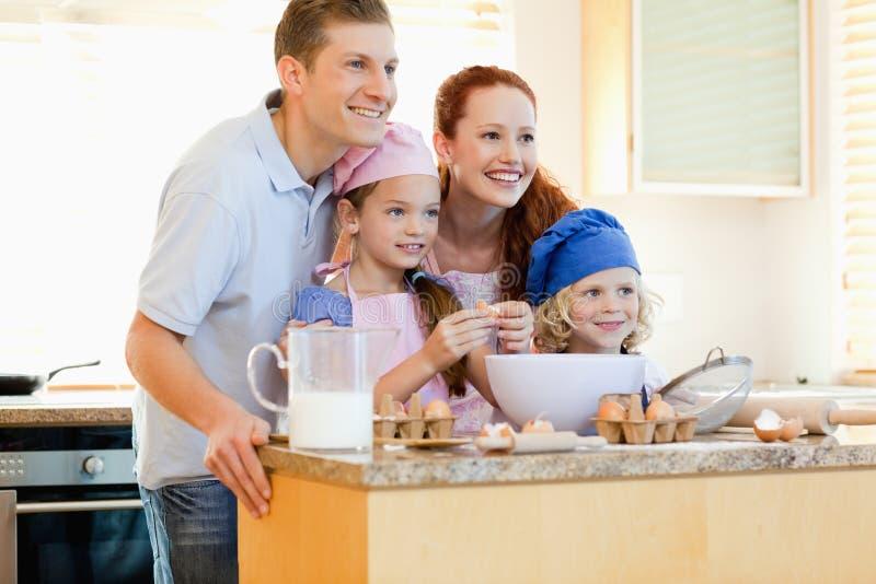 Família na cozinha com ingredientes do cozimento imagem de stock