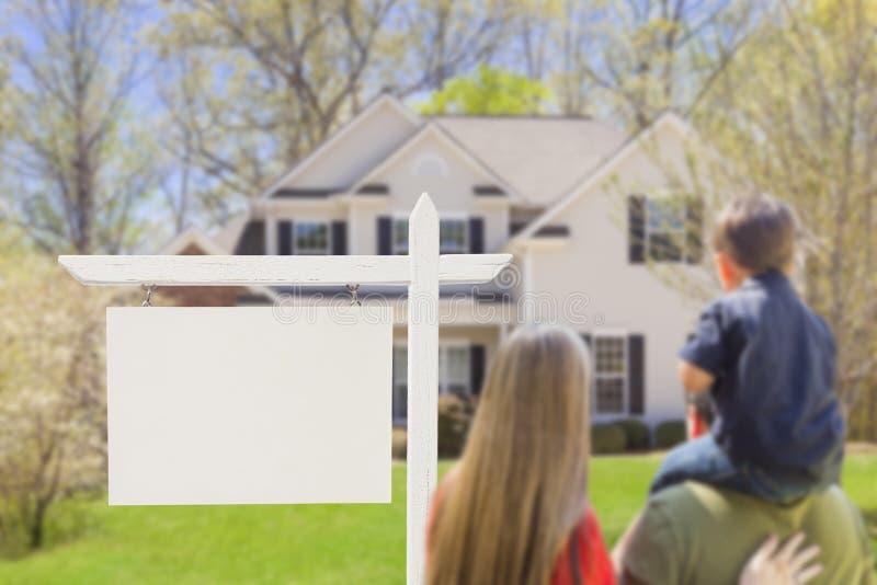 Família na frente do sinal e da casa vazios de Real Estate fotografia de stock