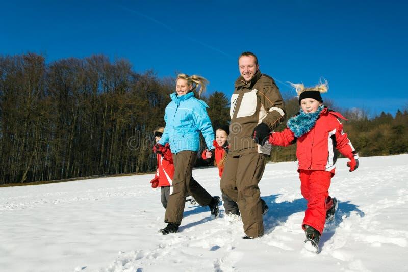 Família na neve em um monte fotografia de stock royalty free