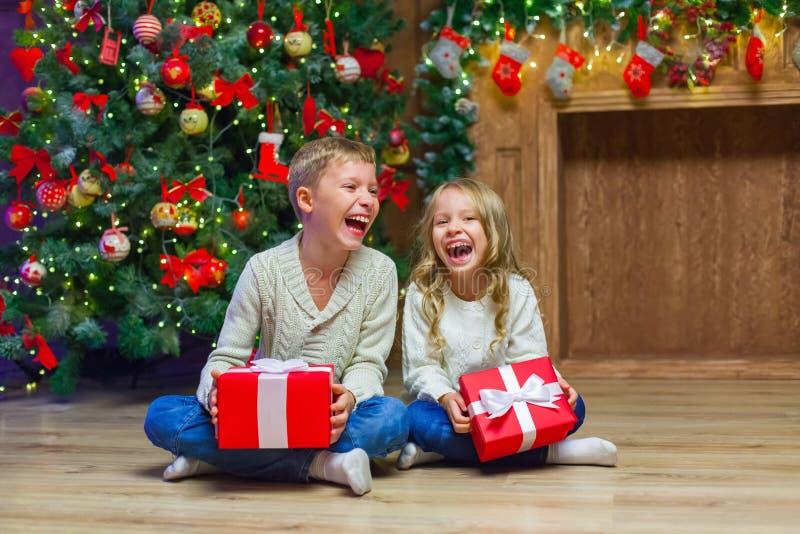 Família na Noite de Natal na chaminé Crianças que abrem presentes do Xmas foto de stock