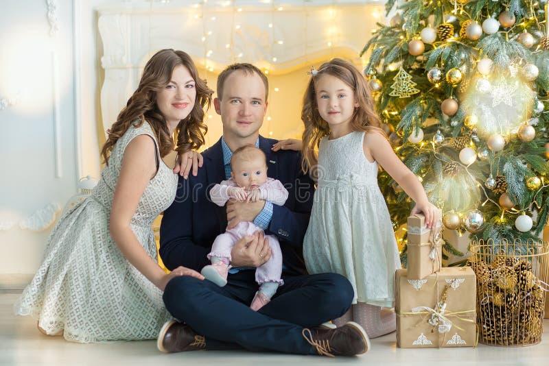 Família na Noite de Natal na chaminé Crianças que abrem presentes do Xmas Crianças sob a árvore de Natal com caixas de presente V fotografia de stock