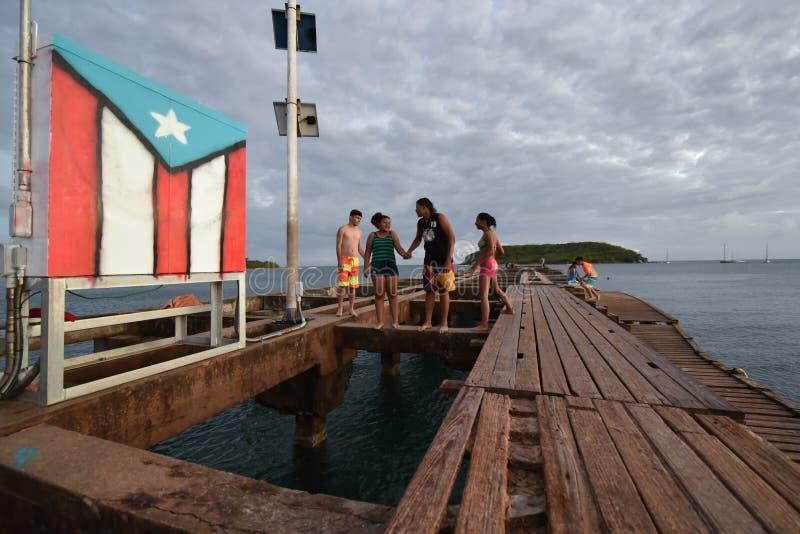Família na praia ao lado da bandeira em Vieques, Porto Rico fotos de stock