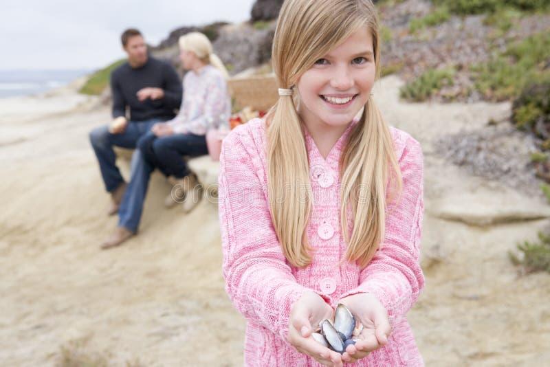 Família na praia com piquenique e menina com escudo fotos de stock royalty free