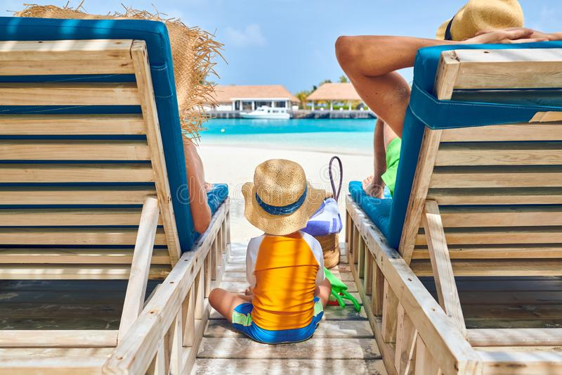 Família na praia em vadios de madeira da cama do sol imagem de stock