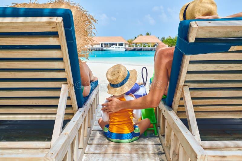 Família na praia em vadios de madeira da cama do sol fotos de stock royalty free