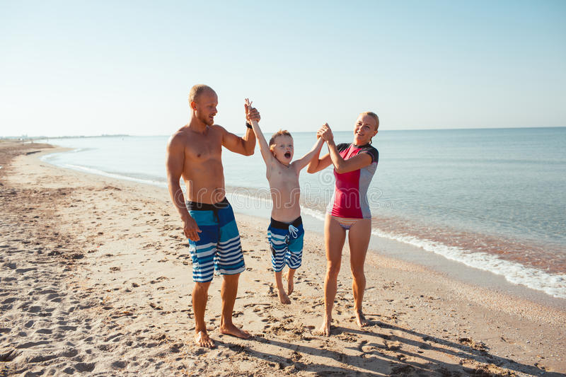 Família na praia no por do sol fotografia de stock
