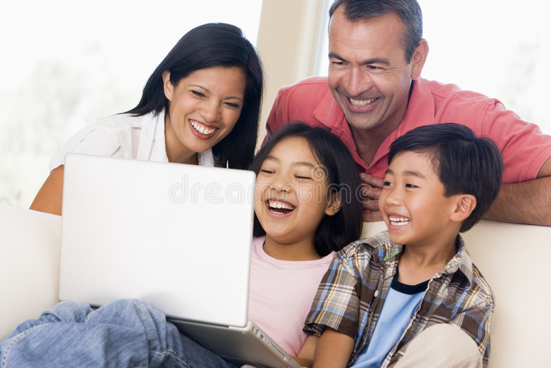Família na sala de visitas com portátil foto de stock