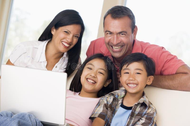 Família na sala de visitas com portátil imagem de stock