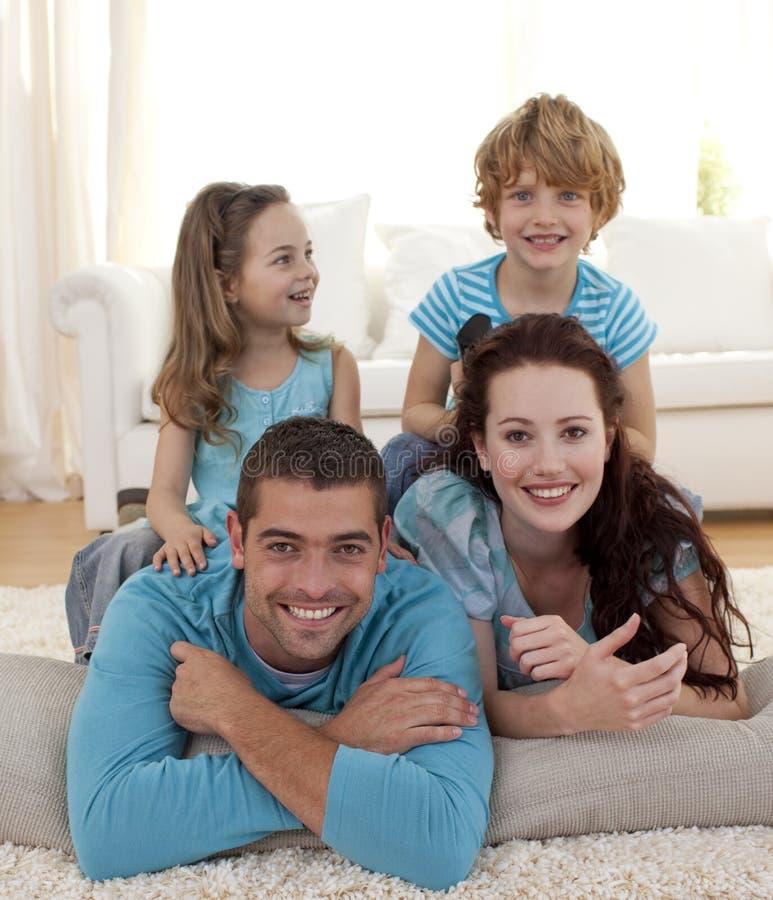 Família no assoalho na sala de visitas