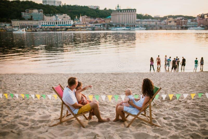 Família no beira-mar em nivelar o café ao ar livre A mãe e o pai e dois filhos sentam-se nos vadios do sol, olhando o por do sol  fotos de stock