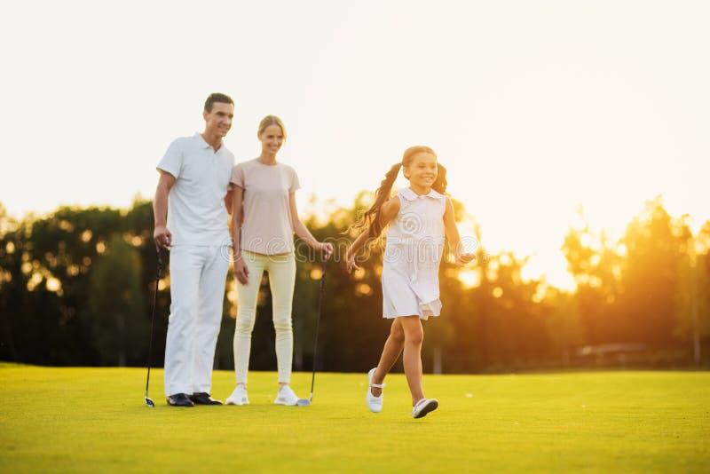 A família no campo de golfe, menina feliz que corre através do campo, seus pais está estando com clubes de golfe atrás fotos de stock