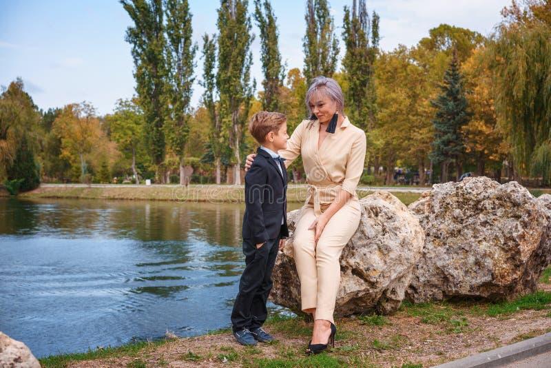 Família no parque pelo lago, pela mãe e pelo filho fotografia de stock
