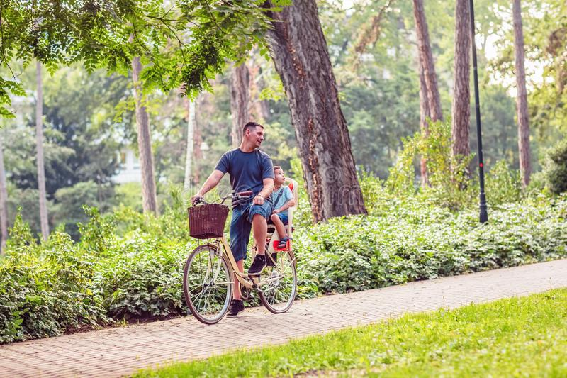 Família no passeio do ciclo no pai e no filho do campo que montam uma bicicleta imagens de stock royalty free