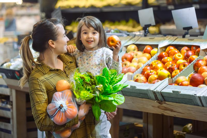 Família no supermercado Da sua filha pequena alimento de sorriso e de compra da mamã nova bonita e imagens de stock