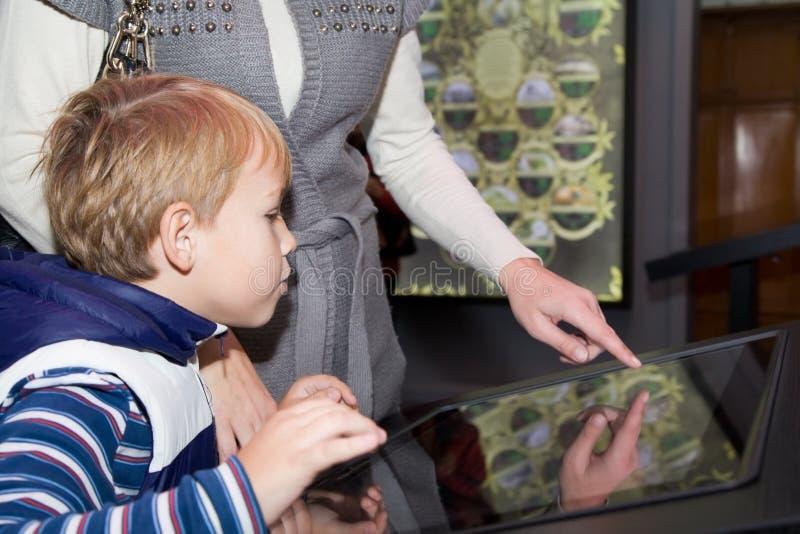 Família no tela táctil interativo do relógio do museu fotografia de stock royalty free