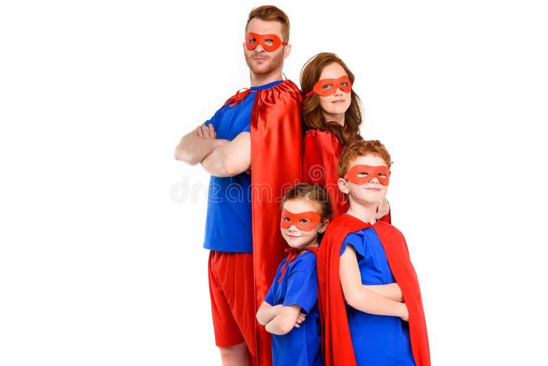 família nos trajes do super-herói que estão com braços cruzados e que olham a câmera fotografia de stock royalty free