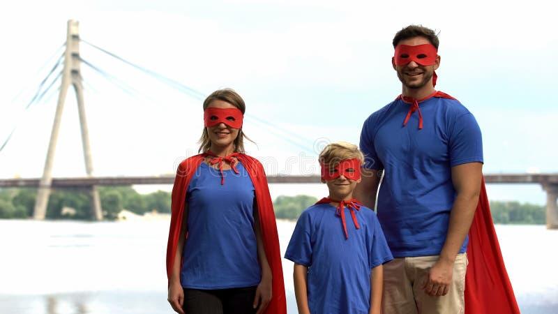 Família nos trajes do superman que levantam para a câmera, o apoio parental e o conceito do cuidado imagens de stock