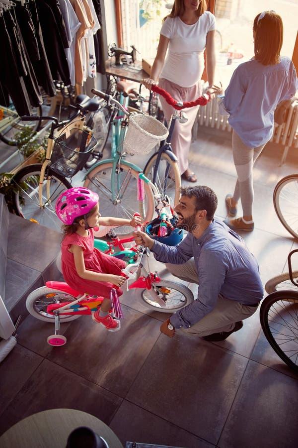 Família nova à bicicleta nova de compra na opinião superior da loja foto de stock