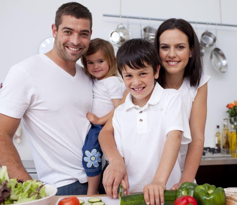 Família nova afectuosa que cozinha junto