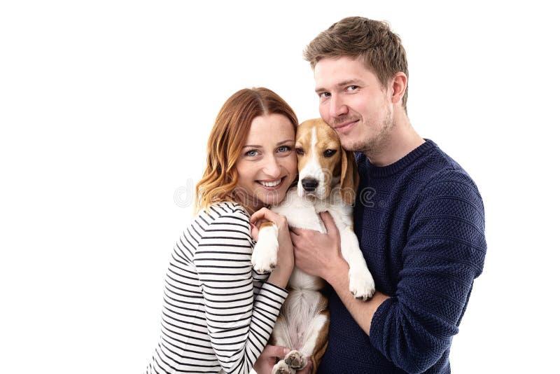 A família nova alegre está abraçando seu cachorrinho imagens de stock royalty free