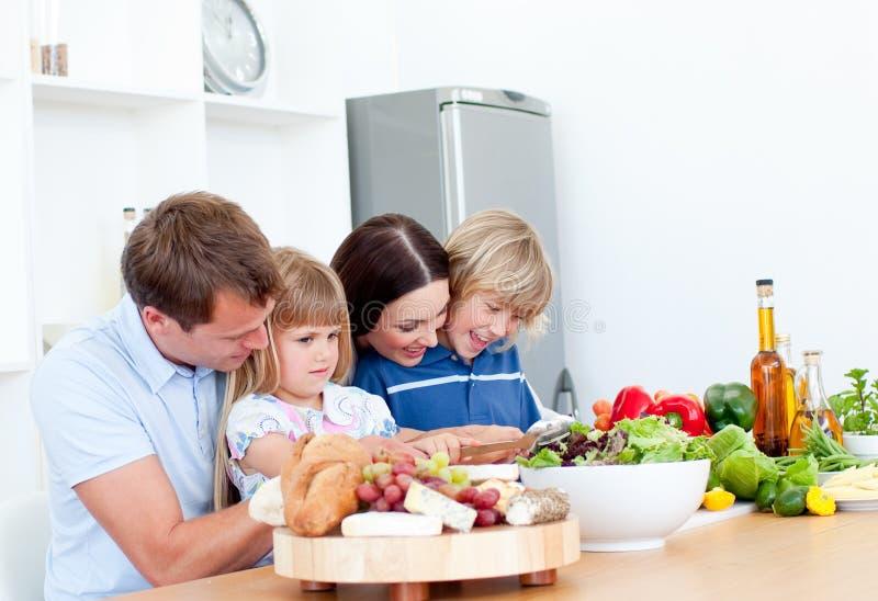 Família nova alegre que cozinha junto