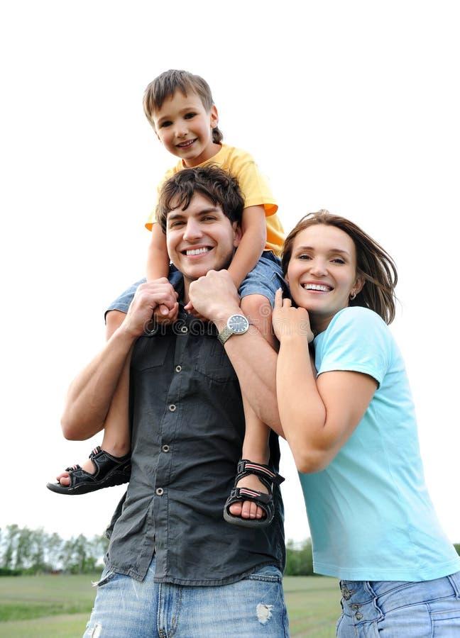 Família nova bonita feliz que levanta ao ar livre