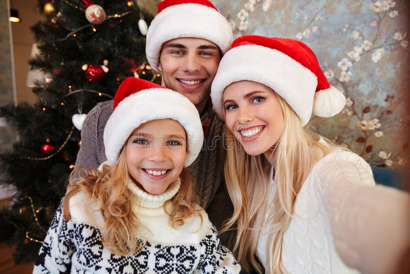 Família nova bonita no chapéu do ` s de Santa que toma o selfie perto do Natal imagem de stock royalty free