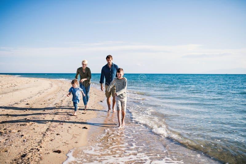 Família nova com as duas crianças pequenas que correm fora na praia imagem de stock royalty free