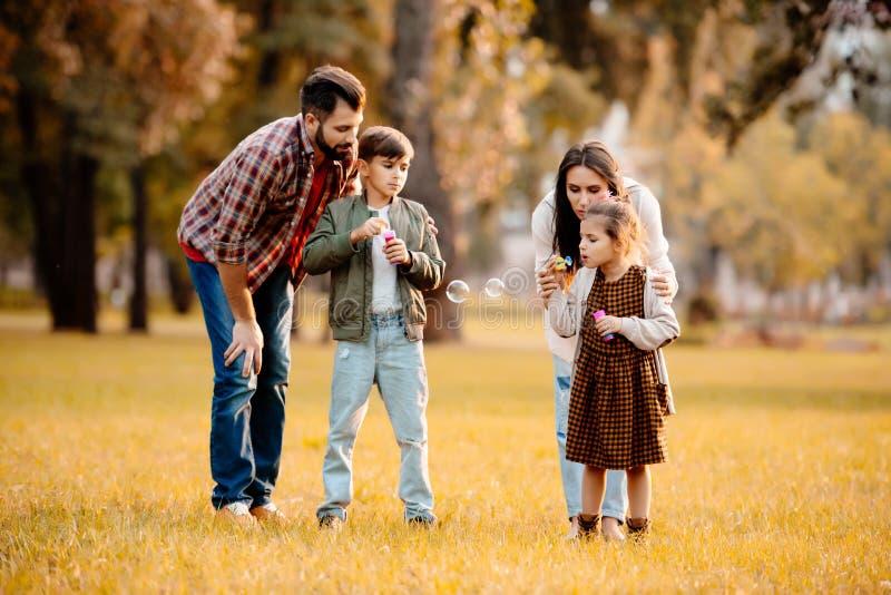 Família nova com as duas crianças que jogam com bolhas de sabão imagens de stock
