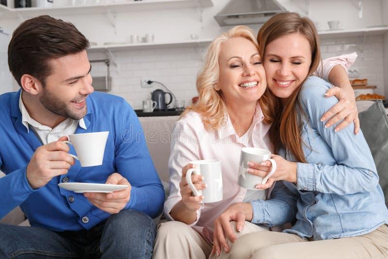 Família nova com café bebendo do fim de semana da sogra em casa fotografia de stock