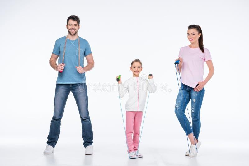 Família nova com cordas de salto no branco fotos de stock royalty free