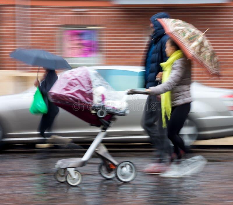 Família nova com a criança pequena no carrinho de criança foto de stock royalty free