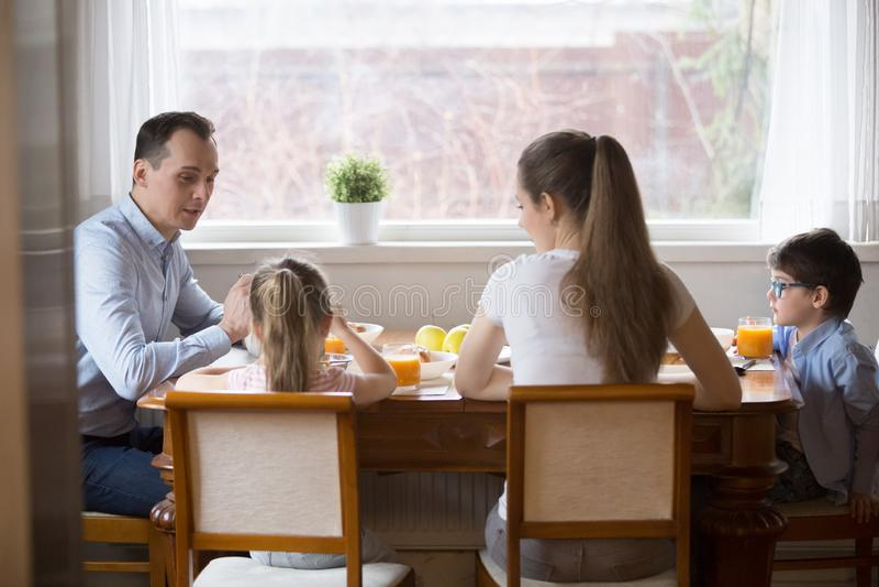 A família nova com crianças aprecia o café da manhã saudável em casa foto de stock royalty free