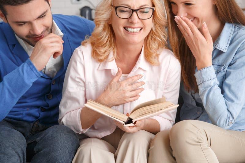 Família nova com fim de semana da sogra em casa que ri do close-up da história foto de stock