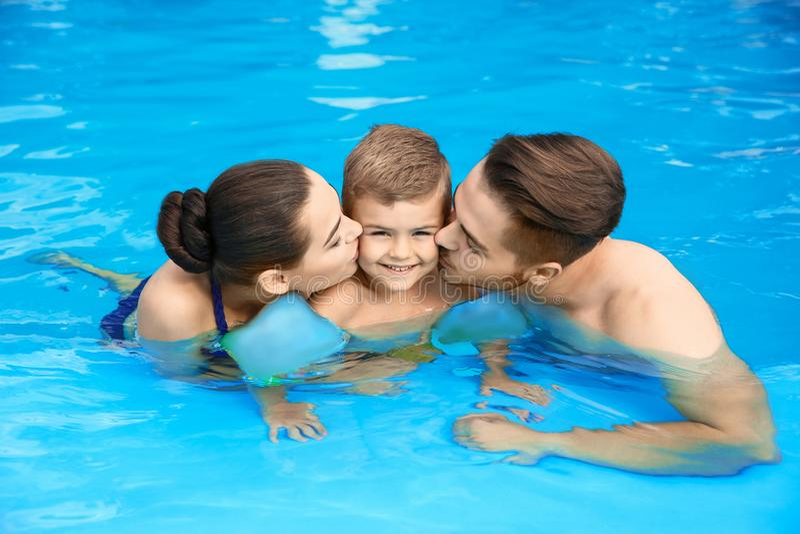 Família nova com o filho pequeno na piscina imagens de stock royalty free