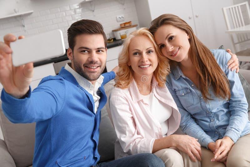 Família nova com o fim de semana da sogra em casa que toma fotos do selfie fotografia de stock royalty free