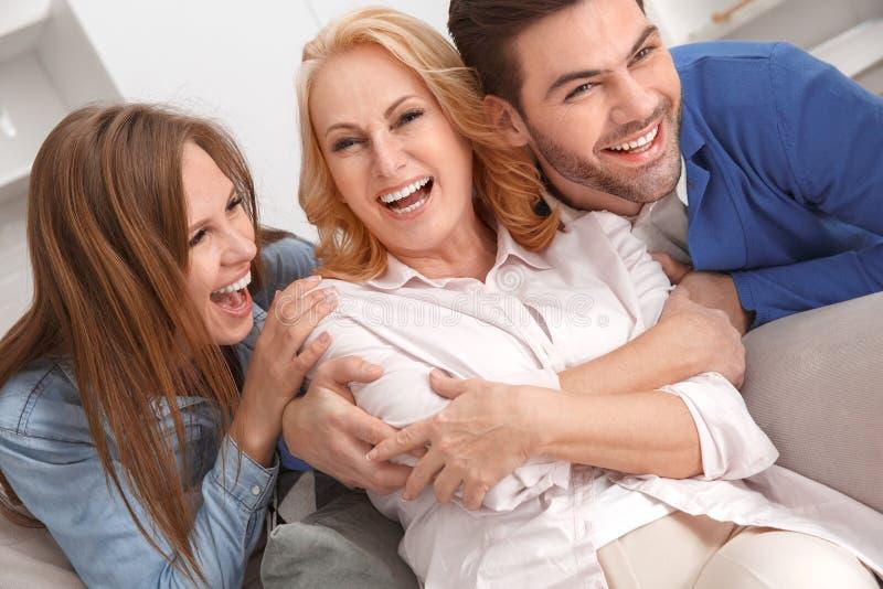 Família nova com o riso do fim de semana da sogra em casa alegre imagem de stock