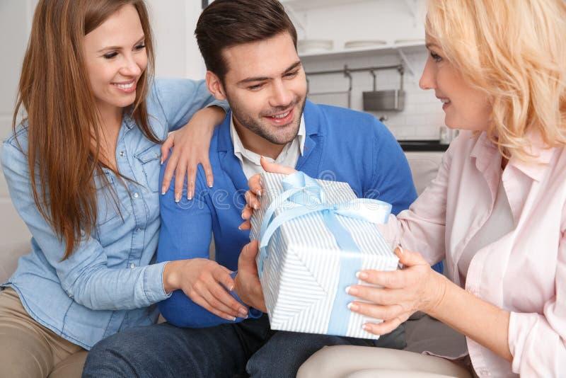 Família nova com presente de aniversário do fim de semana da sogra em casa foto de stock royalty free