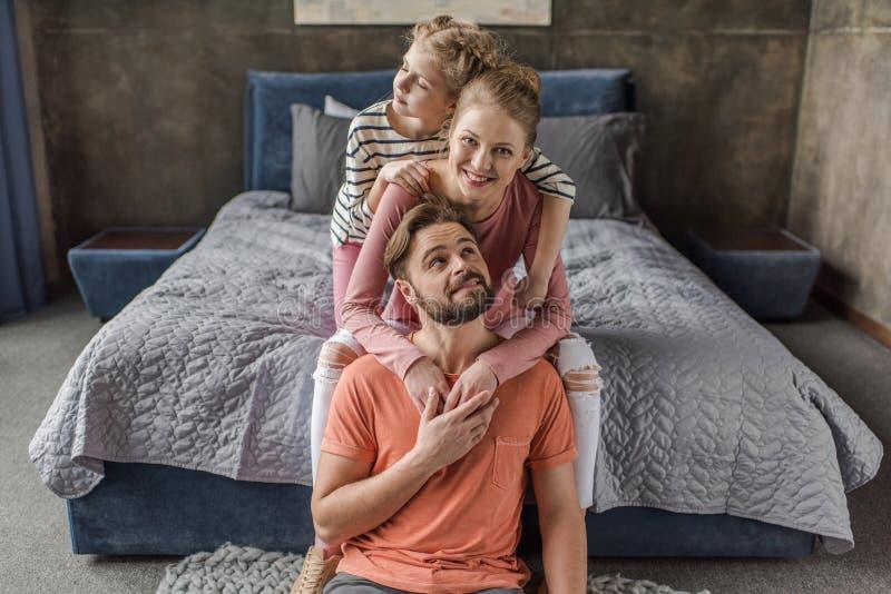 Família nova com a uma criança que senta-se junto e que abraça no quarto fotos de stock royalty free