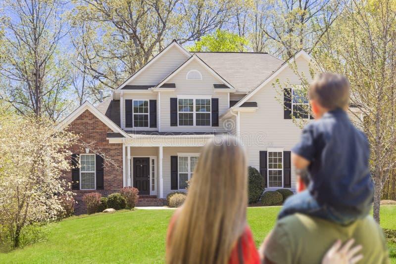 Família nova da raça misturada que olha a casa bonita imagens de stock royalty free