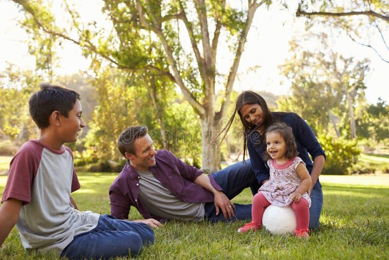 Família nova da raça misturada que relaxa com bola de futebol em um parque fotografia de stock