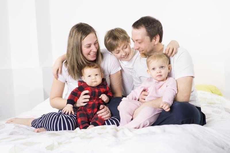 Família nova de cinco membros que tem o divertimento na cama imagem de stock royalty free