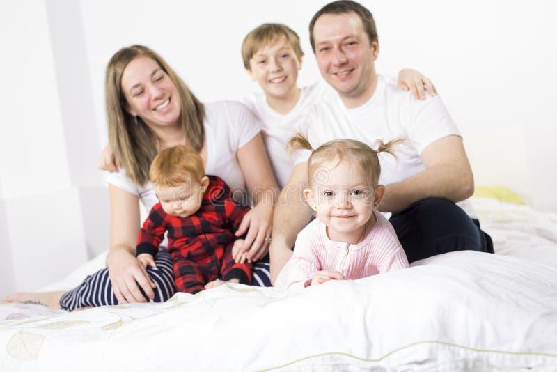 Família nova de cinco membros que tem o divertimento na cama imagem de stock