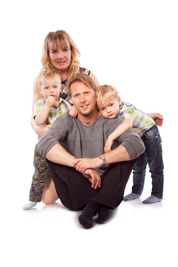 Família nova de sorriso feliz caucasiano com as duas crianças que sentam o imagens de stock royalty free